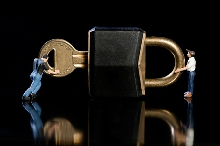 Two miniature workmen checking a key and padlock on black background with reflection, conceptual of a safety and security check