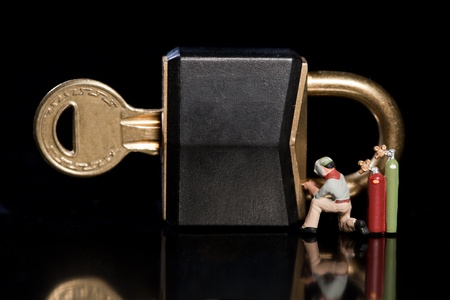 Conceptual image of a tiny miniature workman repairing a security breach to a padlock and key with an acetylene welder Stock Photo