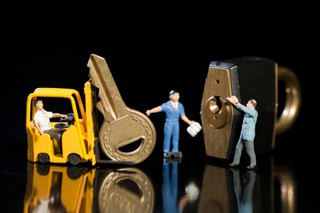 A team of miniature model workmen offloading a key and padlock from a forklift to enhance security