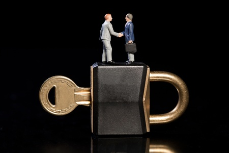 Two toy model miniature businessmen shake hands standing on top of a padlock and key, conceptual od business security