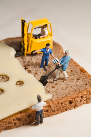 A tiny model figure of a foreman directs his miniature team in the making of a cheese sandwich using a forklift and loading equipment