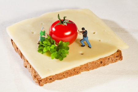 Figurine placing a tomatoe upon a cheese sandwich Stock Photo