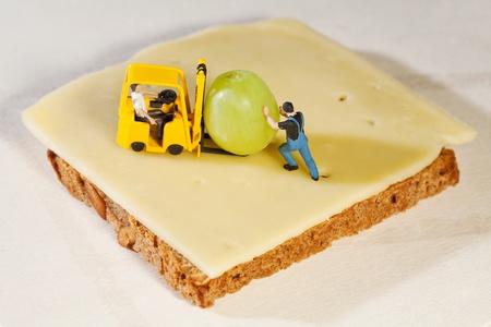 making a sandwich: Workmen figurines making a sandwich with heavy equipment