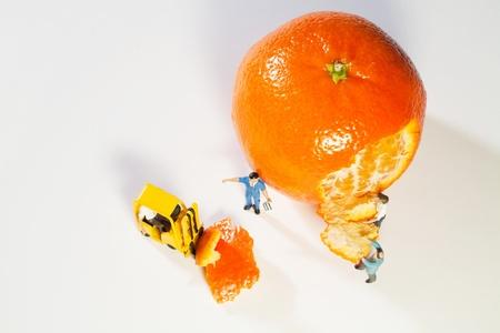 Dos figuras de la escala utilizando una carretilla elevadora para transportar lejos de c�scaras de una naranja Foto de archivo - 12568034