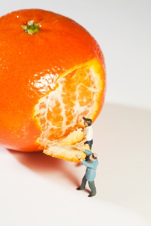 Two small figurines peeling a full size orange