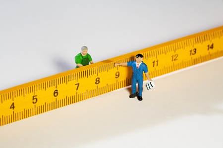 Two fugurines showing concept of scale with a common ruler Stock Photo