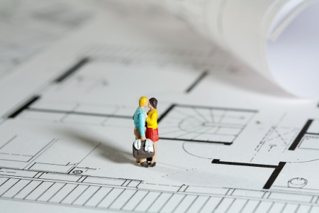 New home concept with tiny miniature models of a couple with a new stylised home