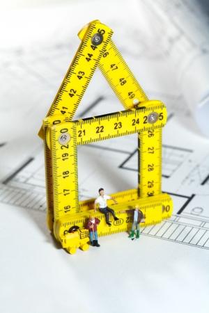 Conceptual image of tiny miniature workmen on a blueprint building site Stock Photo