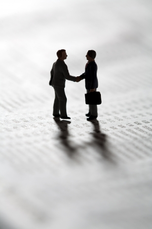 business transaction: Two tiny miniature figurines of businessman standing in silhouette on a statistical document sealing a business transaction with a handshake Stock Photo