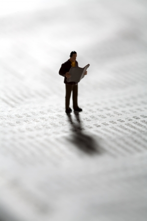 Tiny miniature model of an investor checking market updates in the newspaper as he stands on a financial document
