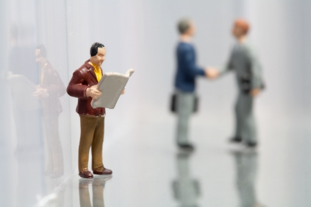 Tiny little miniature model of a man reading the newspaper while taking a break at work with two colleagues shaking hands in the background photo