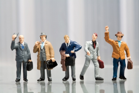 Line-up of tiny miniature figures of male office workers in varying attire on a reflective surface with copyspace Stock Photo