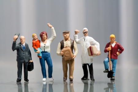 miniature people: Line of diverse tiny miniature model people in population demographics representing a cross section of the community including a housewife, artisan, labourer, and professionals Stock Photo
