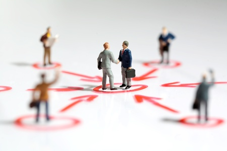 Two tiny miniature businessmen shake hands in the centre of a networking web surrounded by linked colleagues offering support and teamwork in business Stock Photo