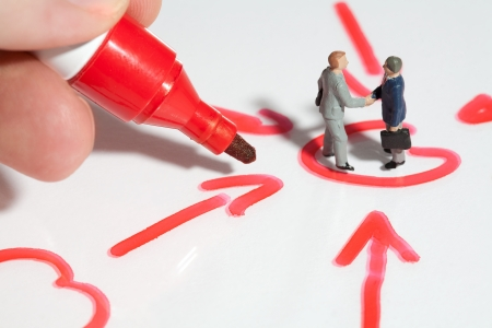 Two tiny miniature businessmen giving a business handshake sealing the deal standing in a schematic handrawn diagram of converging arrows with fingers holding a red marker pen for scale comparison Stock Photo