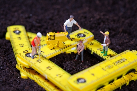 compacting: Tiny miniature maintenance team repairing a stylised road with hammer drill and compacting roller while one man works in a pit