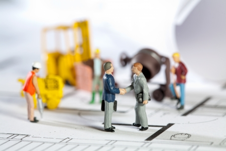 Tiny toy model figures of tradesmen and workers in the construction industry with their equipment on a building site on a blueprint plan for a house design photo