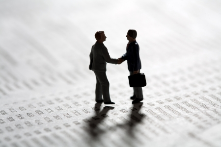 Two tiny miniature figurines of businessman standing in silhouette on a statistical document sealing a business transaction with a handshake Stock Photo
