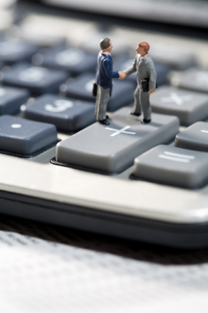 Miniature toy models of men standing on the keys of a calculator shaking hands on a business agreement or accounting deal