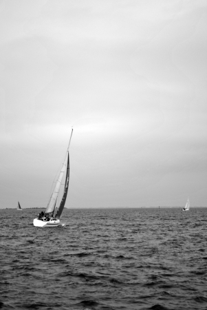 A crew sailing their sailboat on a stormy day photo