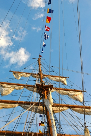 Nautical flags hanging from a large wooden mast Stock Photo
