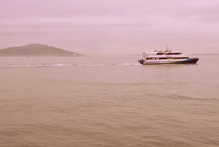 Ferry boat heading traveling past Alcatraz Island on a foggy day. Horizontal Format.  Editorial