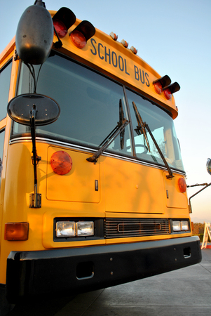 Close up of a yellow school bus on the blacktop on a beautiful sunny day