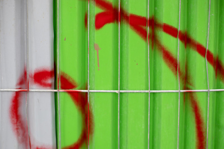 Red spray paint on a green and white metal Stock Photo