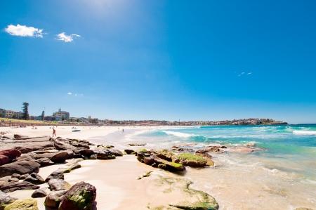 rocky coast and beach with blue sky and sun