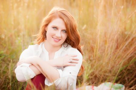 red haired girl: ragazza dai capelli rossi in un campo erboso Archivio Fotografico