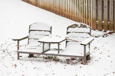 Empty park bench in winter snow