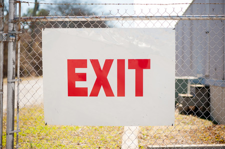 exit sign on a chain link fence