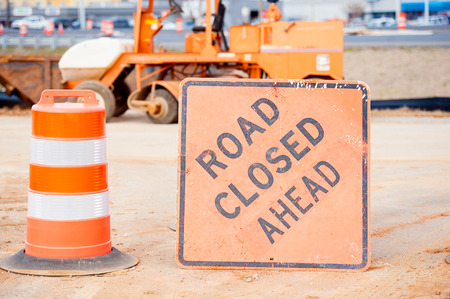 Ornage barrel and road closed sign at construction site heavy equipment  Stock Photo