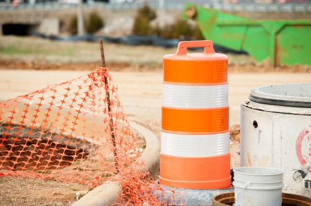 Orange blockage net and barrel at construction site