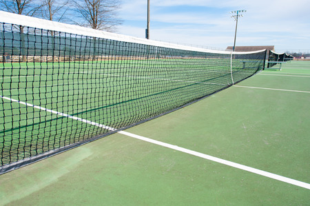 Tennis court with net and blue sky