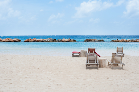 wooden beach chairs on white sand with blue water and white clouds