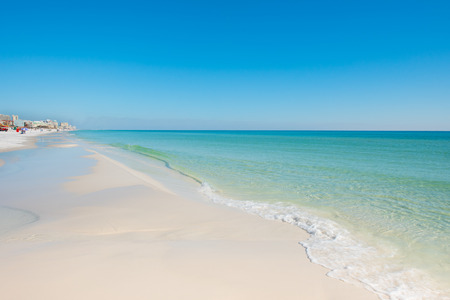 white sand beach with waves and blue green water and blue sky