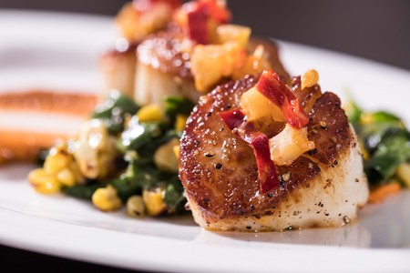Close up seared scallop on greens