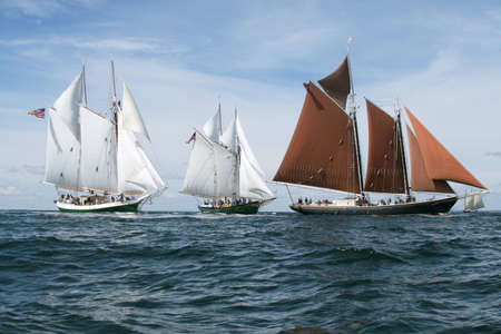 Schooners sail over the ocean waves in the bay near a harbor off of Gloucester. photo