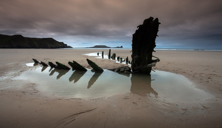 helvetia: Rhossili bay is in the Gower peninsular south Wales the photo shows Worms Head on the left and the remains of the ship The Helvetia a Norwegian barque which was wrecked during a storm in 1887. Stock Photo