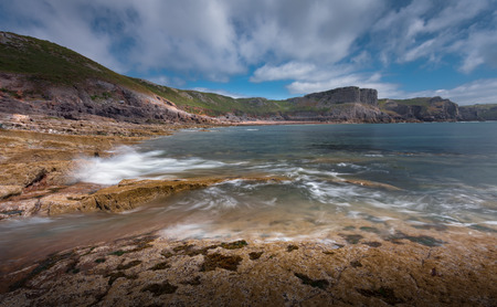 swirling: Steep cliffs and swirling tide around Fall Bay and Mewslade Bay near Rhossili on the Gower peninsular south Wales Stock Photo
