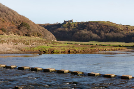 stepping: Pennard Castle and the stepping stones over the river in Three Cliffs Valley on the Gower Peninsula, Swansea. Editorial