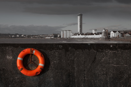 devise: Life saver on the West Pier in Swansea overlooking Swansea Bay and the Meridian Tower Stock Photo