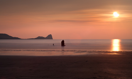 helvetia: Sunset at Rhossili Bay and Worms Head showing remains of the ship The Helvetia, a Norwegian barque, which was wrecked during a storm in 1887 on the Gower peninsula, South Wales