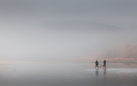 keep fit: Two men choose to keep fit by paddleboarding in heavy misty conditions on the river at Three Cliffs Bay, Gower