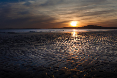 outgoing: Sunset at Aberavon beach on an outgoing tide with Swansea on the horizon Stock Photo