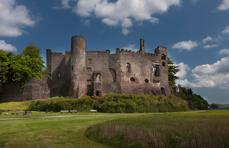 boat house: Laugharne Castle, a medieval castle on the river Taf estuary in Carmarthenshire, South Wales, with Dylan Thomass Boat House tucked away to the right.