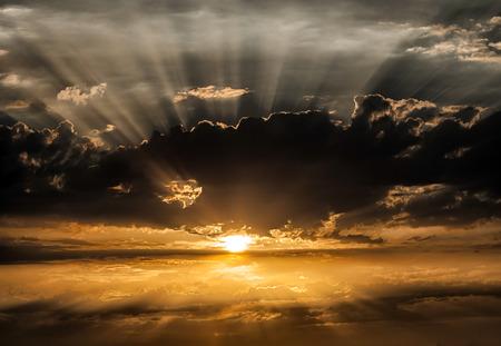 ciel dramatique que le soleil se cache derrière un nuage noir.