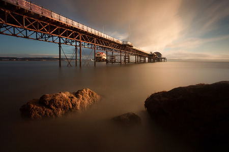 Sunrise at Mumbles Pier showing the old and new lifeboat stations, Swansea