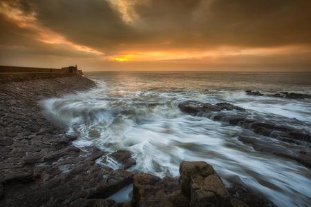 choppy: Sunrise at Porthcawl Sunrise and a choppy sea at Porthcawl lighthouse in South Glamorgan, South Wales